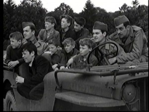 School children sitting in a Willys Jeep with US personnel. Davy Fitzsimons believes their names are as follows : Jackie Gillispie, Edmond O'Conner, Samuel Houston, Tom Paul Hegerty, Leo Devlin. There are also two boys who are evacuees. He believes their names were Robert & Jack Magee.